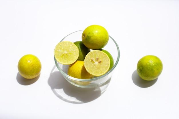 Frische limetten in glasschüssel auf weißem hintergrund.