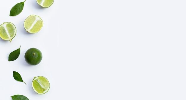 Frische limetten mit grünen blättern auf weißem hintergrund. ansicht von oben