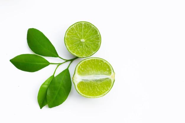 Frische limetten mit grünen blättern auf weißem hintergrund. draufsicht