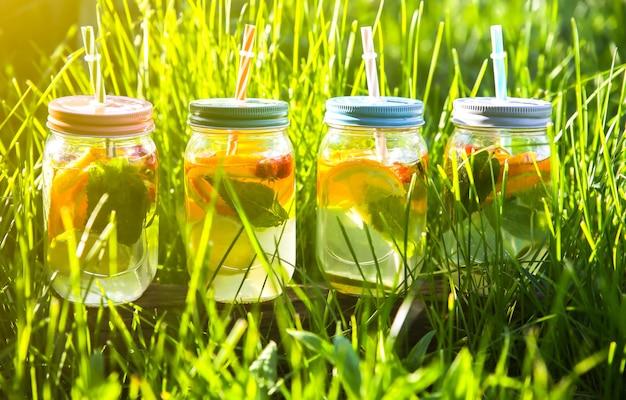 Frische limonade in gläsern mit strohhalmen. hipster-sommergetränke. umweltfreundlich in der natur. zitronen, orangen und beeren mit minze im glas. grünes hohes gras draußen.