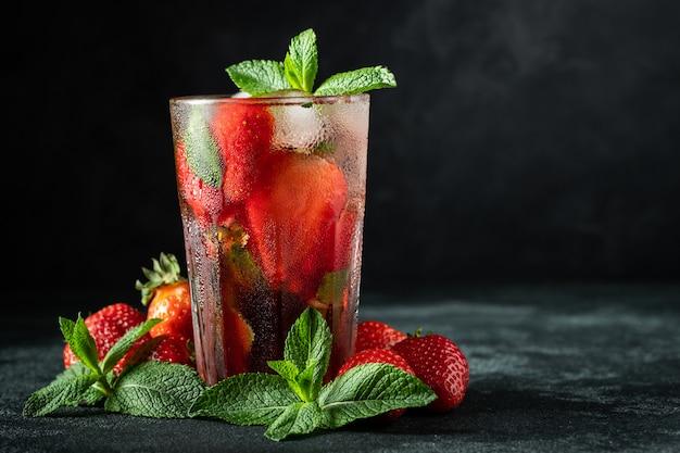 Frische limonade mit eis, minze und erdbeere.