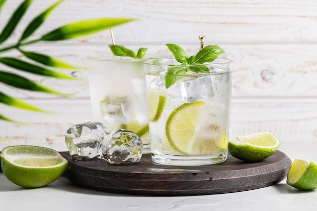 Frische limonade mit eiswürfeln, limetten- und basilikumblättern auf weißem hölzernem hintergrund erfrischender sommercocktail auf dem tisch
