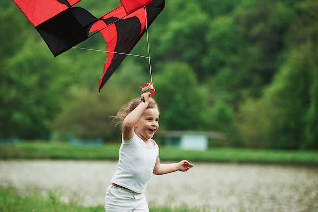 Frische luft. positives weibliches kind, das mit rotem und schwarzem drachen in den händen draußen läuft