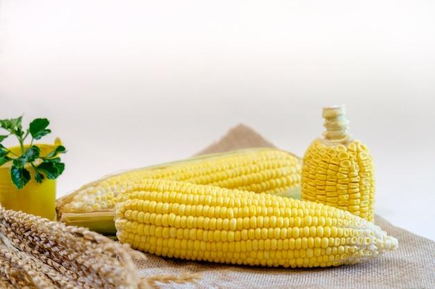Frische maiskörner auf brauner stofftabelle mit reis