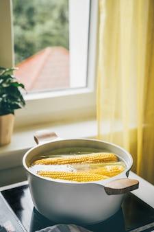 Frische maiskolben kochen in heißem wasser auf dem herd. vegetarisches essen