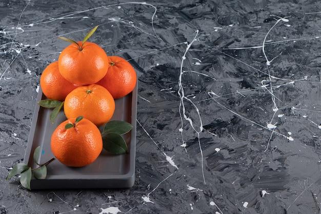 Frische mandarine auf einem holzteller auf der gemischten oberfläche