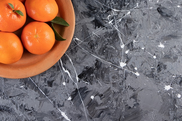 Frische mandarine auf einem teller auf der gemischten oberfläche