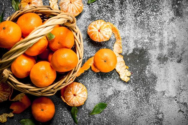 Frische mandarinen in einem korb auf rustikalem tisch.