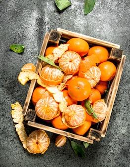 Frische mandarinen in einer alten schachtel auf rustikalem tisch.