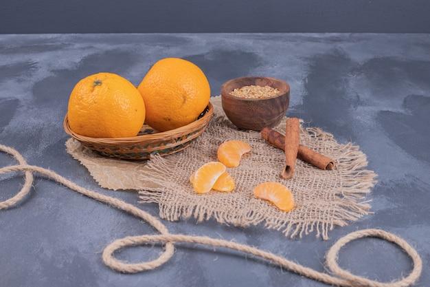 Frische mandarinen in schüssel und zimt auf blauer oberfläche.