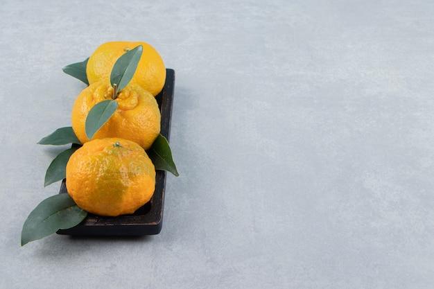 Frische mandarinen mit blättern auf schwarzem teller