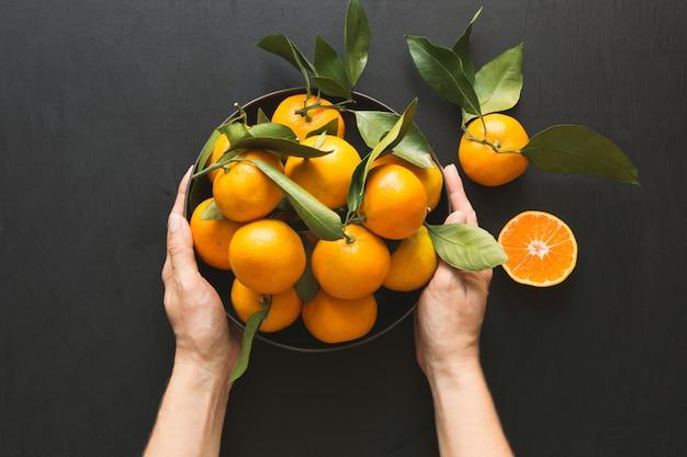 Frische mandarinen mit blättern in der weiblichen hand auf schwarzem. gesundes essen . kopieren sie platz.