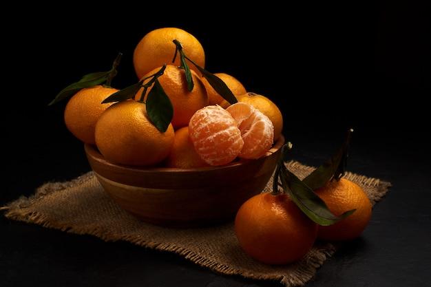 Frische mandarinen mit blättern in einer schüssel auf sackleinen