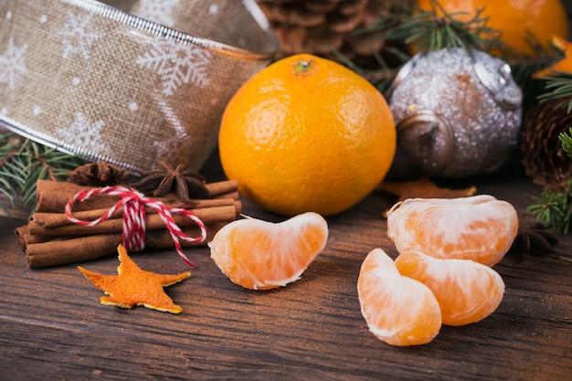Frische mandarinen mit gewürzen und weihnachtsdekoration mit weihnachtsbaum auf dunklem altem holztisch. rustikaler stil. winterferienkonzept.