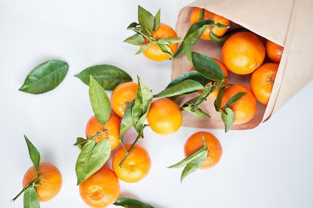 Frische mandarinen mit grünen blättern in einer papiertüte