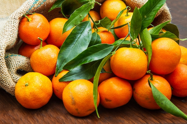 Frische mandarinen tragen mit blättern auf holztisch früchte