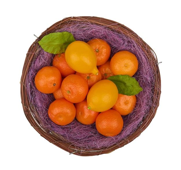 Frische mandarinen und zitronen auf lila stroh in einem korb lokalisiert auf einem weißen hintergrund, draufsicht