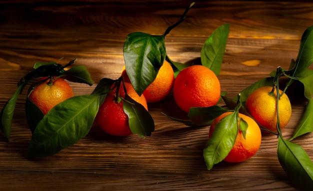 Frische mandarinenfrüchte oder mandarinen mit blättern auf holztisch