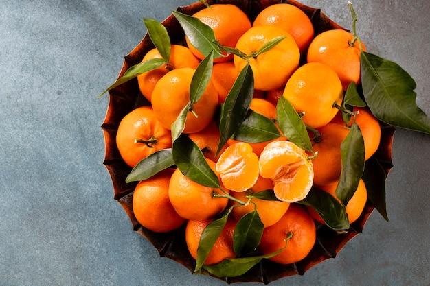 Frische mandarinenfrüchte oder mandarinen mit blättern in der holzkastenoberansicht