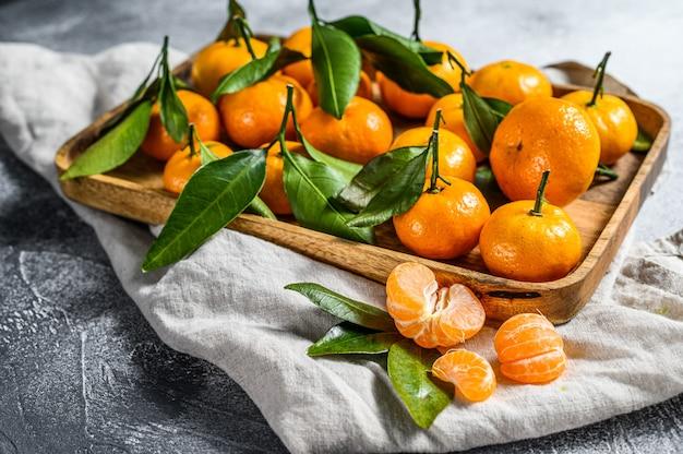 Frische mandarinenfrüchte oder mandarinen mit blättern in einer holzschale. grauer hintergrund. draufsicht