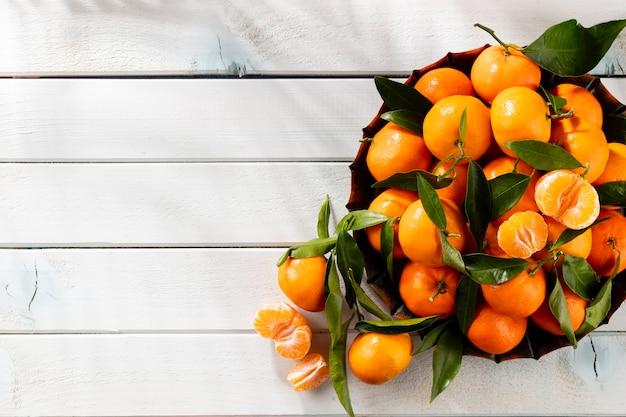 Frische mandarinenfrüchte oder mandarinen mit blättern in holzkiste, ansicht von oben