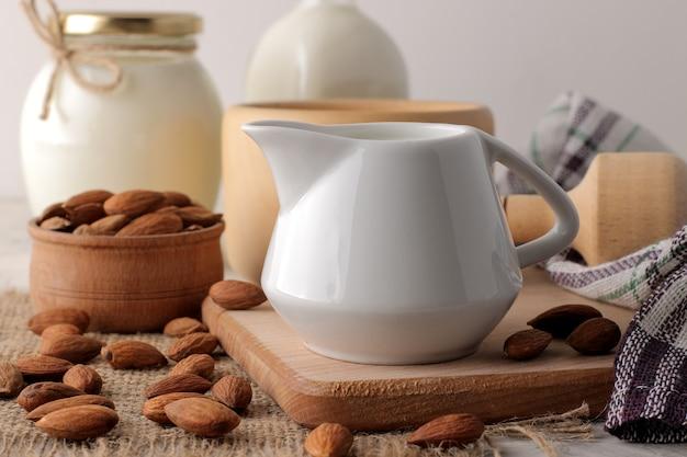 Frische mandelmilch in einem milchkrug und mandelnüssen
