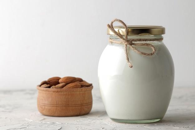 Frische mandelmilch in einer glasflasche und mandelnüsse