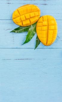 Frische mango - schöne gehackte früchte mit grünen blättern auf hellblauem holzhintergrund