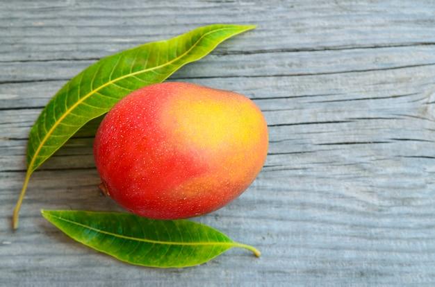 Frische mangofrucht und mangobaumblätter auf holz
