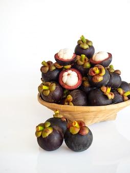Frische mangostanfrucht im bambuskorb auf weißem isolat. gesunde und süße früchte. hohe vitamine.