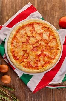 Frische margarita pizza auf rustikalem holztisch