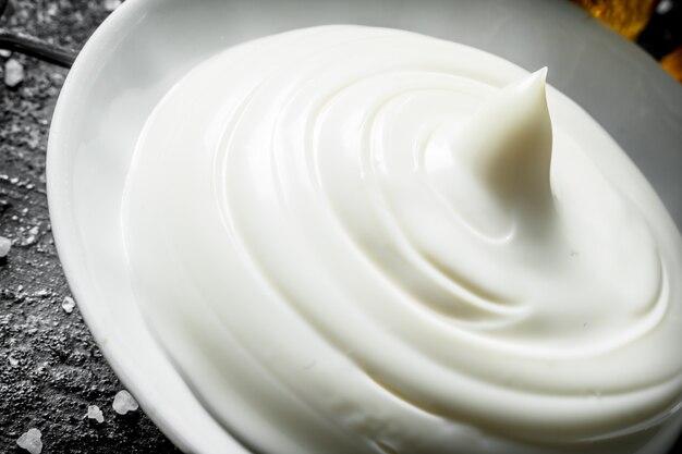 Frische mayonnaise in schüssel. auf rustikalem tisch