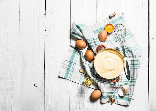 Frische mayonnaise mit den zutaten. auf einem weißen holztisch.