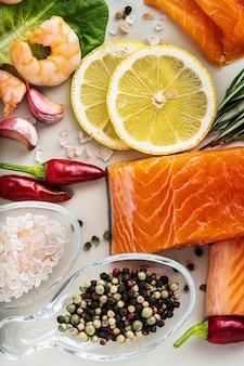 Frische meeresfrüchte auf dem tisch mit gewürzen, gemüse und olivenöl: frischer und geräucherter lachs, garnelen und krabbenstangen für einen supermarkt oder ein fischsushi-restaurant.