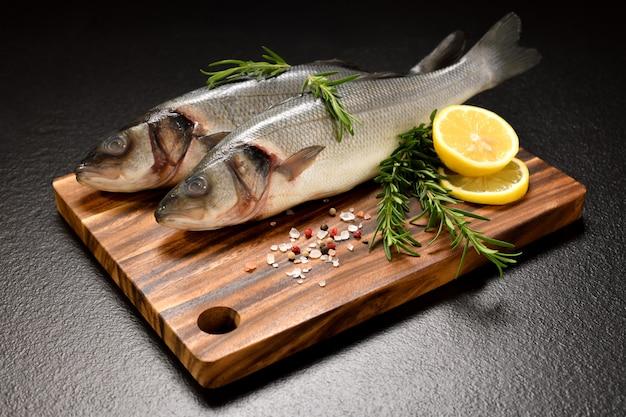 Frische meeresfrüchte seebarschfisch auf schwarzem tisch angeordnet