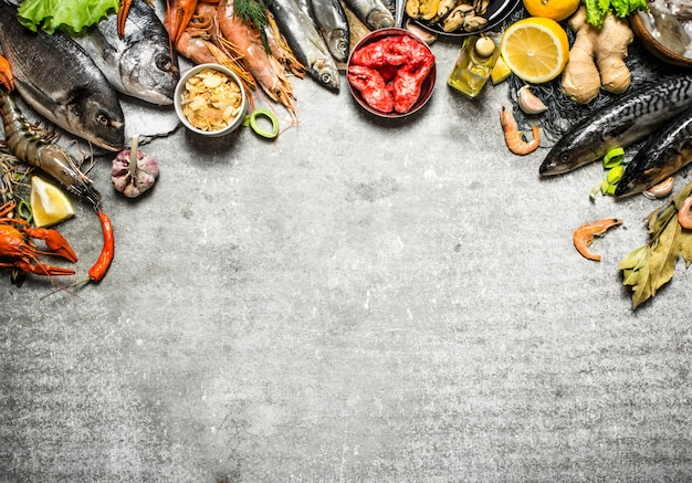 Frische meeresfrüchte verschiedene fische, garnelen und schalentiere mit zitronenscheiben und gewürzen auf einem steinhintergrund