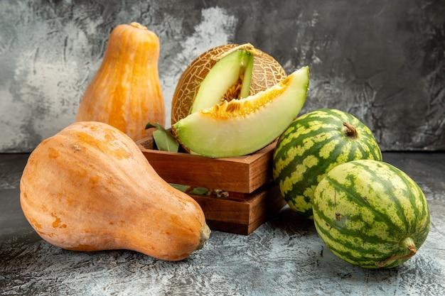 Frische melone der vorderansicht mit kürbis und wassermelone auf dem dunklen hintergrund
