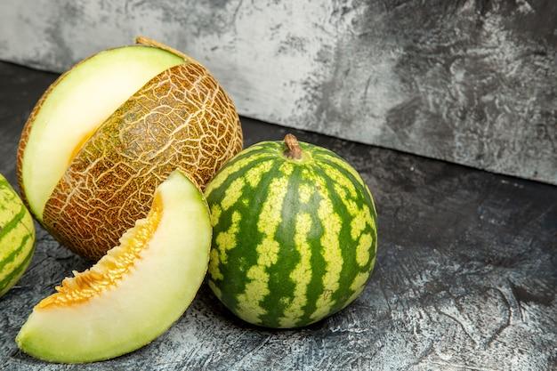 Frische melone der vorderansicht mit wassermelone auf dem dunklen hellen hintergrund