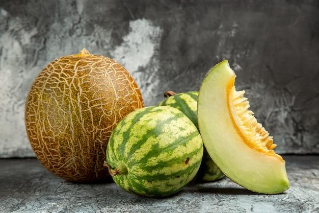 Frische melone der vorderansicht mit wassermelone auf dunklem hellem boden