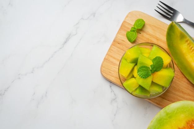Frische melone, in stücke geschnitten, in eine glasschüssel geben