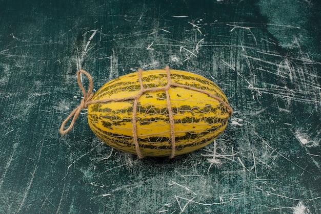 Frische melone mit faden auf marmoroberfläche
