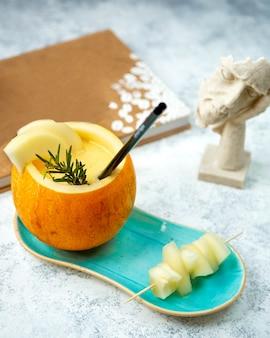 Frische melone mit strohhalm und geschnittener melone