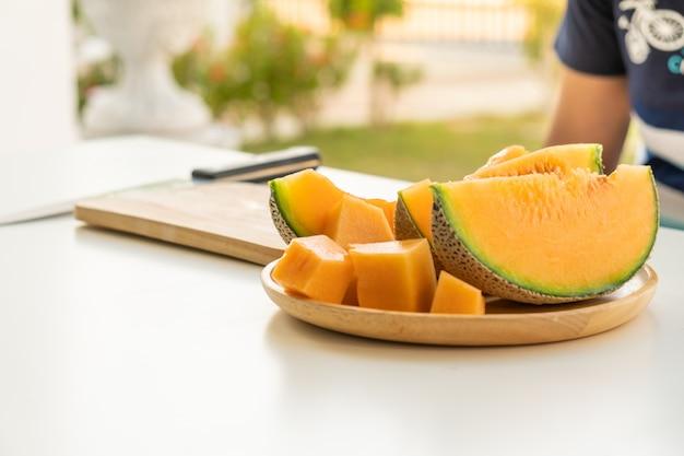 Frische melonen geschnitten auf holzplatte auf weißem tischhintergrund