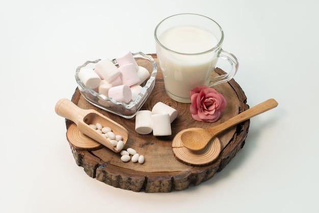 Frische milch der vorderansicht zusammen mit marshmallows auf braunem holz auf weißem, süßem zucker