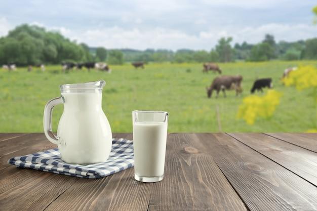 Frische milch im glas auf dunklem holztisch und unscharfer landschaft mit kuh auf wiese gesundes essen. rustikaler stil.