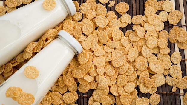 Frische milch in glasflaschen mit cornflakes, milchprodukt-konzept des frühstücks auf holztisch-hintergrund, land rustikaler stillleben-stil