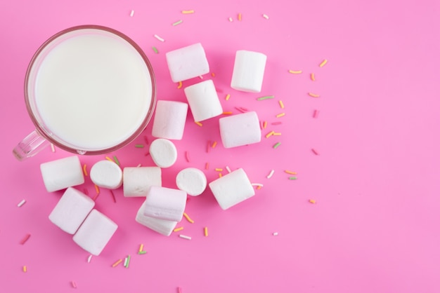 Frische milch von oben mit weißen marshmallows auf rosa, zuckersüßen süßigkeiten