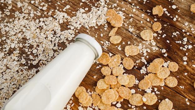 Frische milchflasche auf holzhintergrund mit hafer und getreide. gesundes und natürliches ernährungskonzept