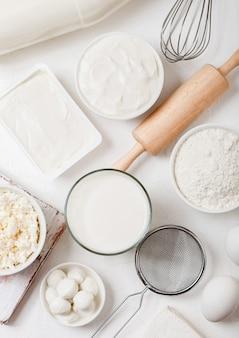 Frische milchprodukte auf weißem tisch. glas milch, schüssel mehl, sauerrahm und quark und eier. schneebesen und nudelholz aus stahl.