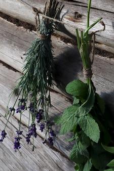 Frische minze und lavendel werden in suspendierter form in bündeln an der frischen luft auf einem hölzernen hintergrund getrocknet. das konzept der duftenden kräuter für die gesundheit